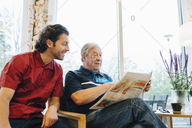 Smiling caregiver sitting by elderly man reading newspaper against window at retirement home