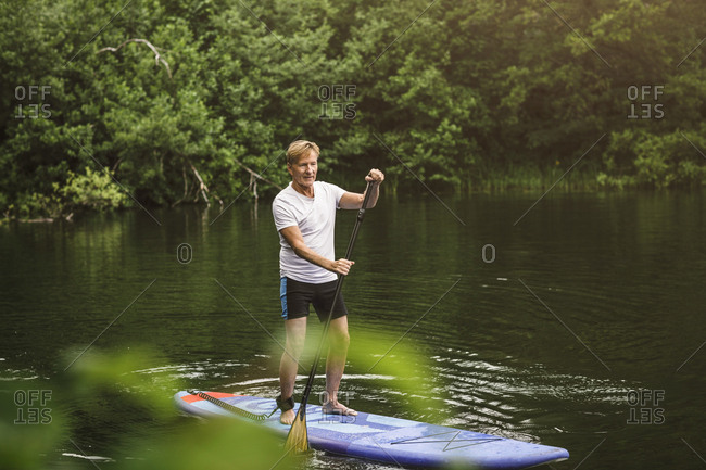 Senior man paddleboarding in sea during SUP course