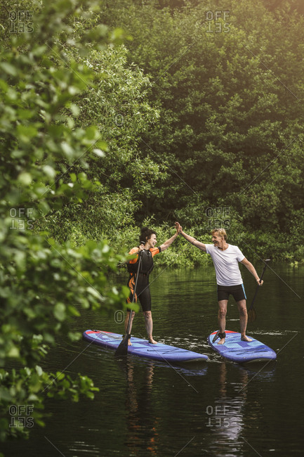 Senior woman and man high-fiving while learning paddleboarding in sea during SUP course