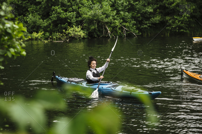 Senior woman paddling kayak in sea during kayaking course