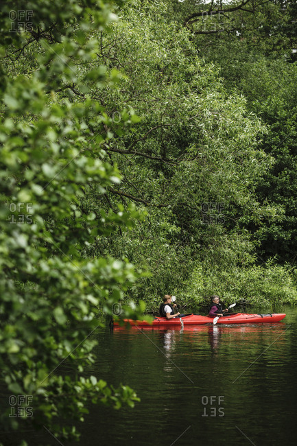 Elderly male and female kayaking in sea during training course