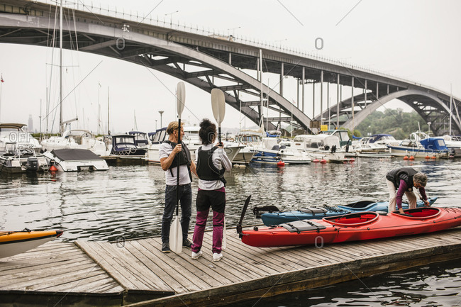 Senior male and females with kayaks and paddles on jetty during kayaking course