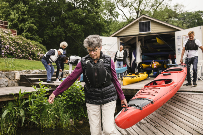 Senior woman and man carrying kayak on jetty during kayaking course