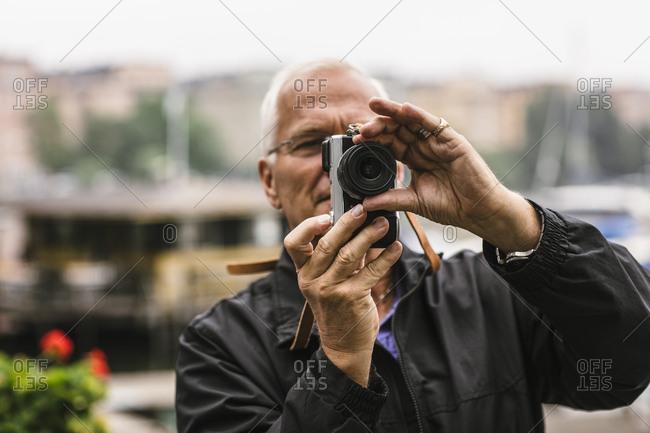 Senior man using camera during photography course