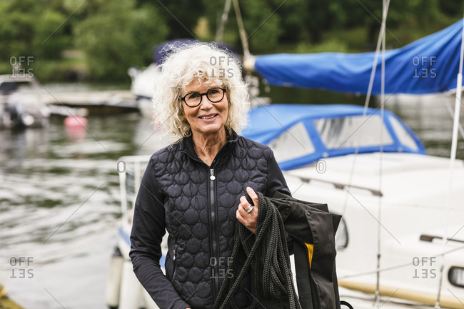 Portrait of confident senior woman holding life jacket and rope while attending boat master course