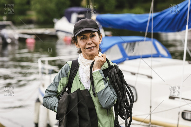 Portrait of confident female instructor holding rope and life jackets against yacht during boat master course