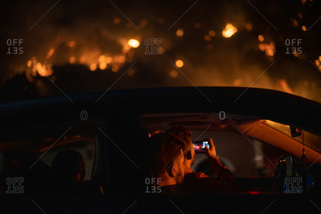 Bystanders watch as a wildfire burns near a highway in Los Angeles, CA