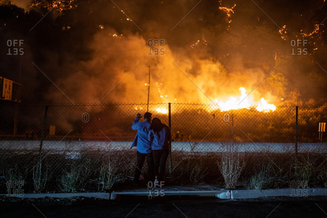 A couple evacuated from their home watch a wildfire burn near a highway in Los Angeles, CA