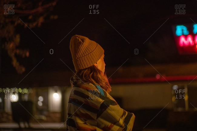 A girl in a patterned vintage coat and beanie hat at a motel parking lot at night