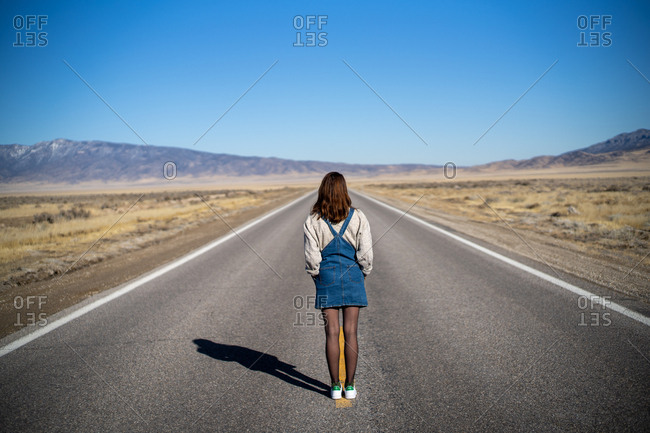 A young woman in vintage clothes stands in the middle of the road in nowhere