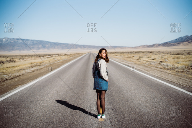 A stylish girl in vintage clothes stands in the middle of the road in nowhere