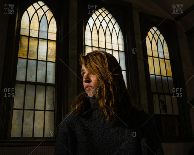 A contemplative woman sits in a church pew with old stained glass