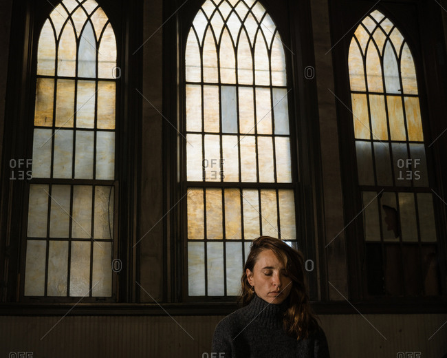 A contemplative woman sits in repose in a church pew with old stained glass