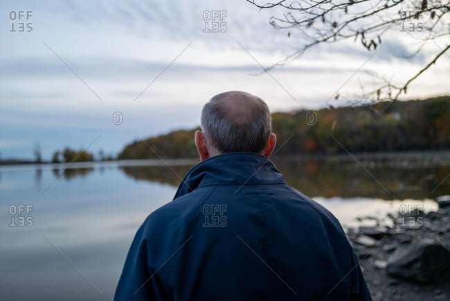 An older man looks towards a lake or river in upstate fall foliage
