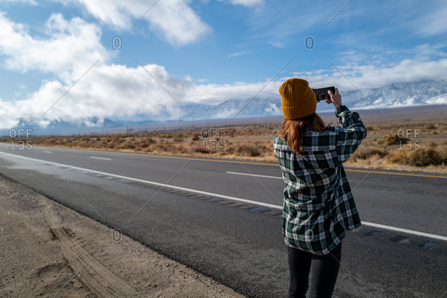 A girl in a vintage flannel takes a selfie near a highway in the Eastern Sierras of California