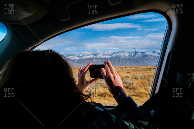 A millennial girl with red hair takes a phone photo out a car window on road trip of mountains in Eastern Sierras, California