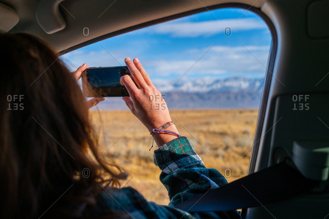 A millennial girl with red hair takes a phone photo out the window on a road trip of mountains in the Sierra Nevadas, California