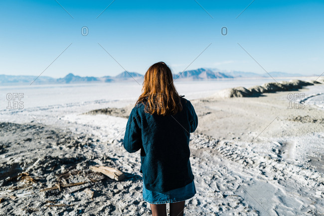 A stylish woman in vintage denim walks carefully on a salt pan in the middle of nowhere