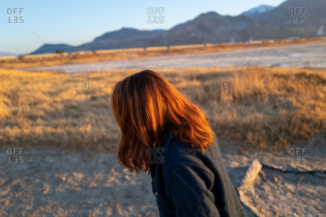 A young woman walks in fields of wheat at golden hour near salt flats