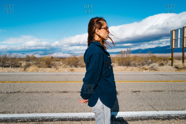 A stylish young woman with hands clasped in wind storm on a road trip through Mojave desert
