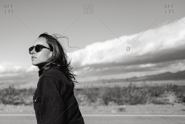 A stylish young woman in sunglasses on a road trip through Mojave desert