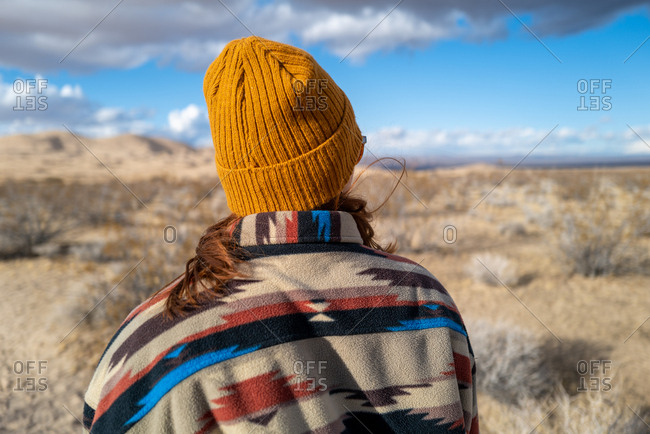 Young woman in Native American patterned jacket and mustard beanie explores Kelso sand dunes in California