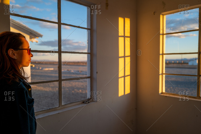 A red haired girl stands in an abandoned building in a desert ghost town