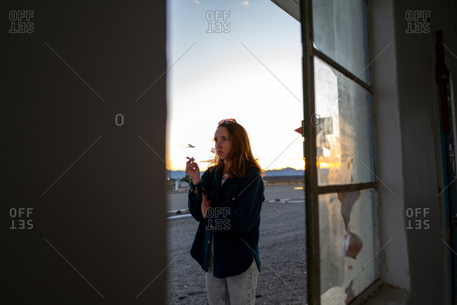A stylish woman smokes outside a window in the California desert at sunset