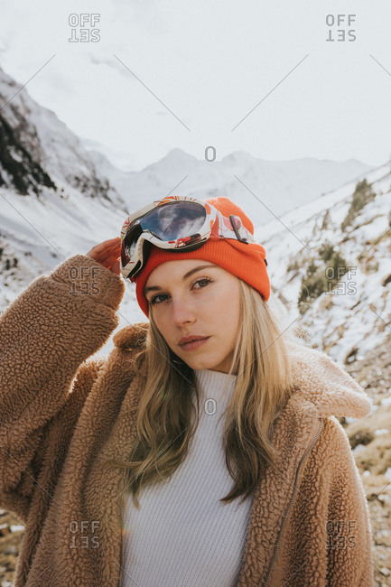 Blonde girl wearing ski goggles on a snowy mountain