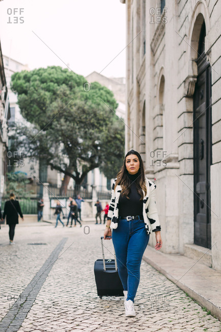 Young woman travelling in Lisbon with a trolley.