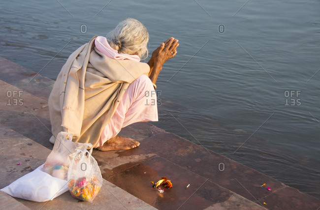 Elder woman praying to Mother Ganges prior to the Arti at Ganga Aarti at Triveni Ghat, Rishikesh, Uttarakhand, India