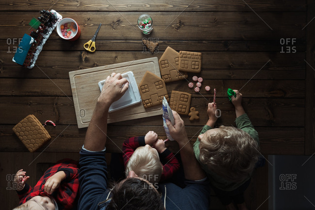 Overhead view of father and kids making a gingerbread house