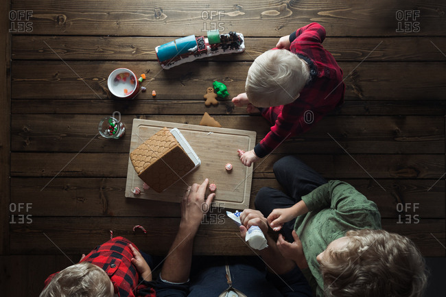 Top view of father and kids making a gingerbread house