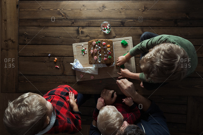 View of father and kids making a gingerbread house from above