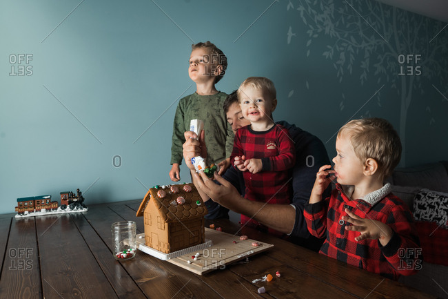 Father and kids making a gingerbread house