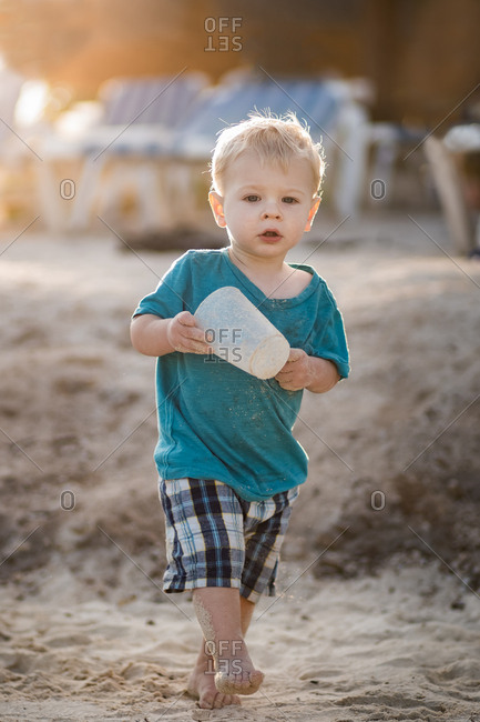 Blond toddler boy walking on sandy beach