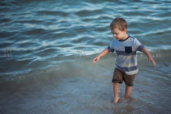 Toddler boy walking in the ocean tide