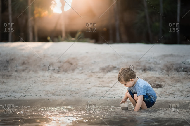 Little boy digging in sandy water with cup