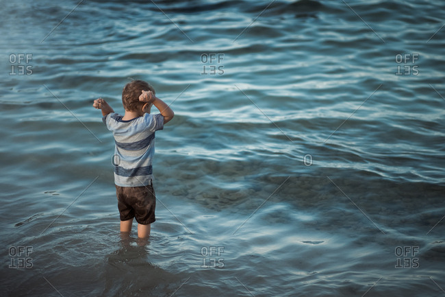 Toddler boy throwing sand into the ocean tide