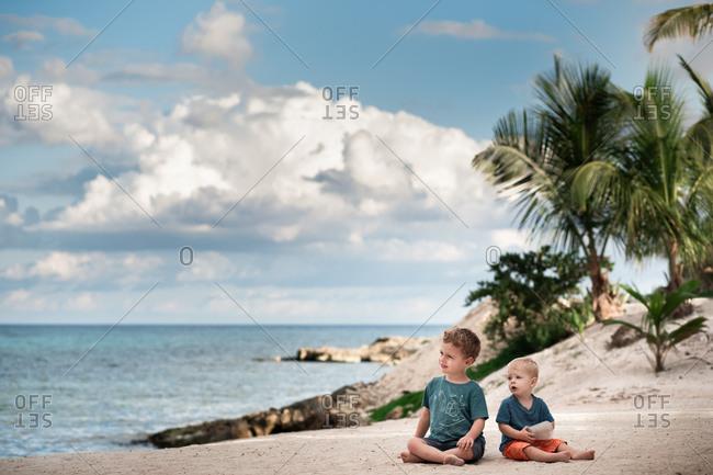 Two boys sitting on tropical beach
