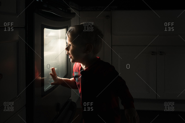 Toddler boy looking into a lit oven