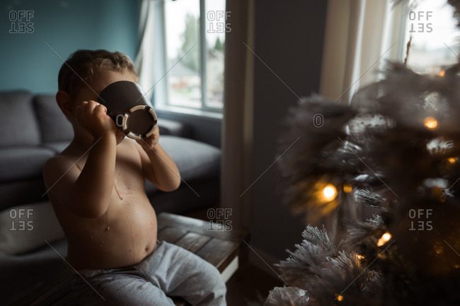Shirtless boy making mess while sipping cocoa by the Christmas tree