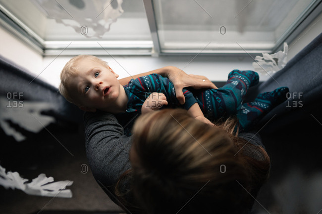 Overhead view of mother holding baby boy by window while he looks at paper snowflakes
