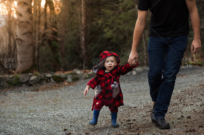 Father walking in the forest with baby boy wearing red robe