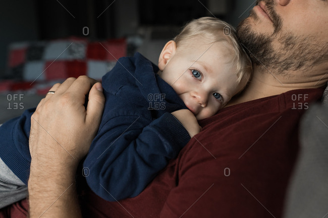 Blue eyed baby resting on father's chest