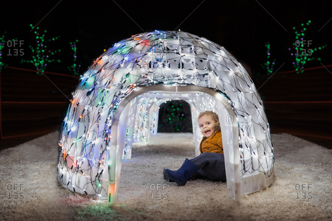 Toddler boy sitting inside illuminated igloo at Christmas time