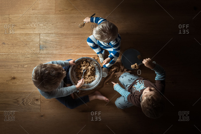 Overhead view of three little boys making and eating cookie dough