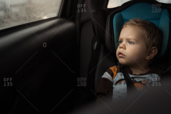 Toddler boy sitting in car seat looking out window