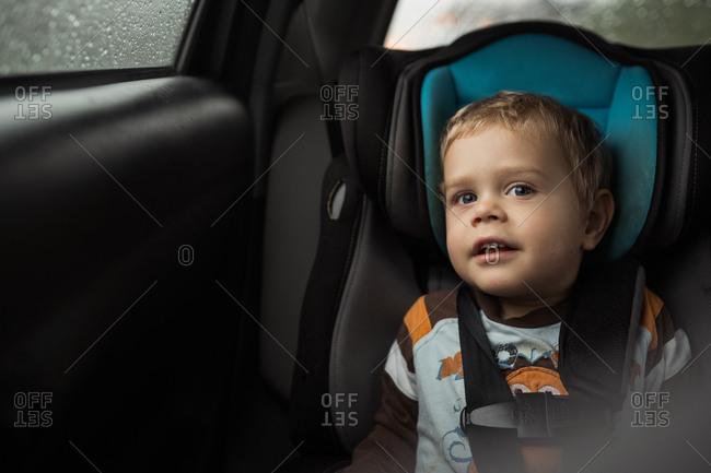 Toddler boy sitting in car seat