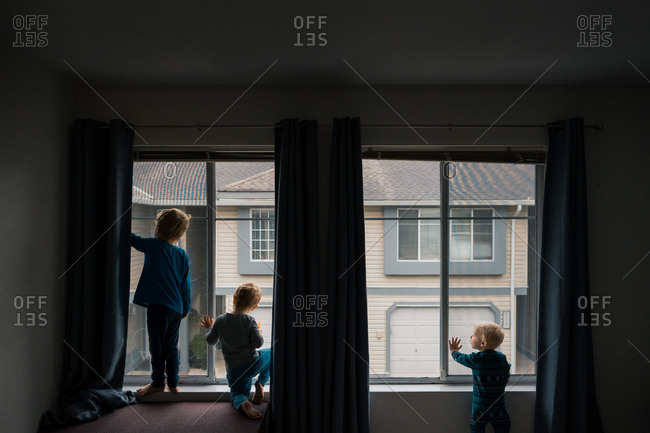 Three little boys looking out apartment window